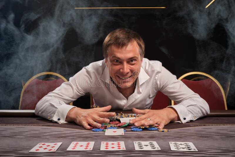 Den stiliga emotionella mannen spelar poker som sitter på tabellen i kasino arkivbild
