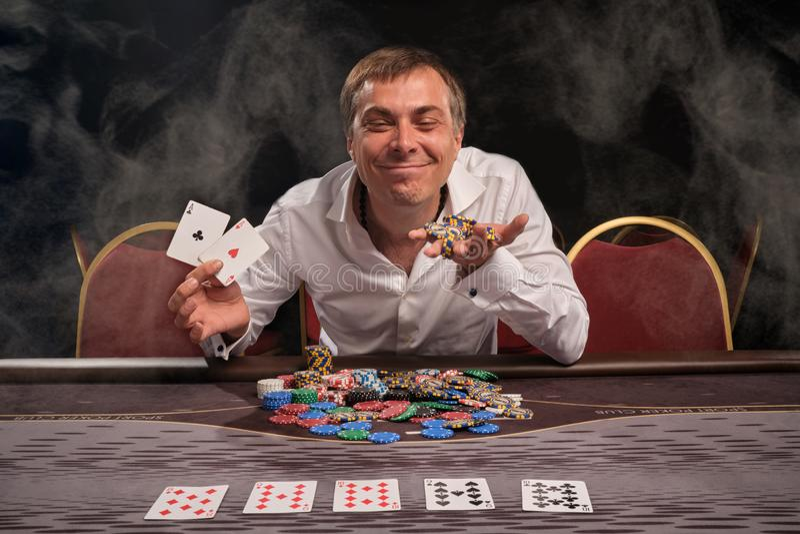 Den stiliga emotionella mannen spelar poker som sitter på tabellen i kasino arkivfoton