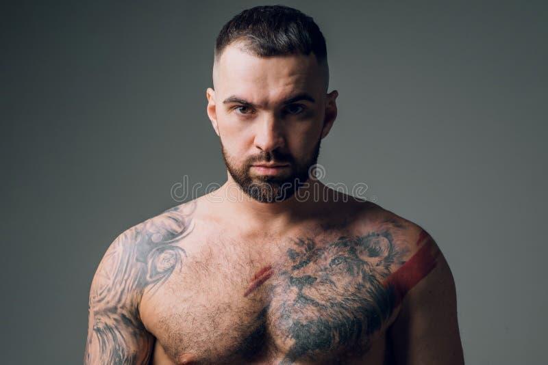 Den stiliga enorma skäggiga mannen med tatueringen ser kameran royaltyfria bilder