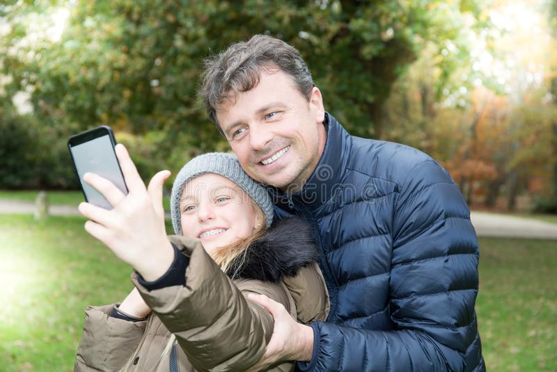 Den stiliga fadern med den gulliga blonda dottern gör selfie fotografering för bildbyråer