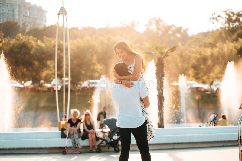 Den stiliga grabben vrider en härlig flicka på en bakgrund av en springbrunn royaltyfri foto