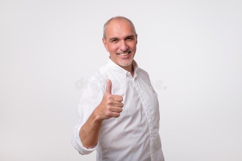 Den stiliga höga mannen i den vita skjortan visar upp tummen Han tillfredsställs med hans hälsa och finansiella conditio royaltyfri fotografi