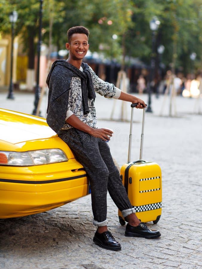 Den stiliga handelsresanden f?r den unga mannen med bagage och kuper ett kaffe som placeras p? en gul huvtaxi fr?n flygplats Skju royaltyfri foto