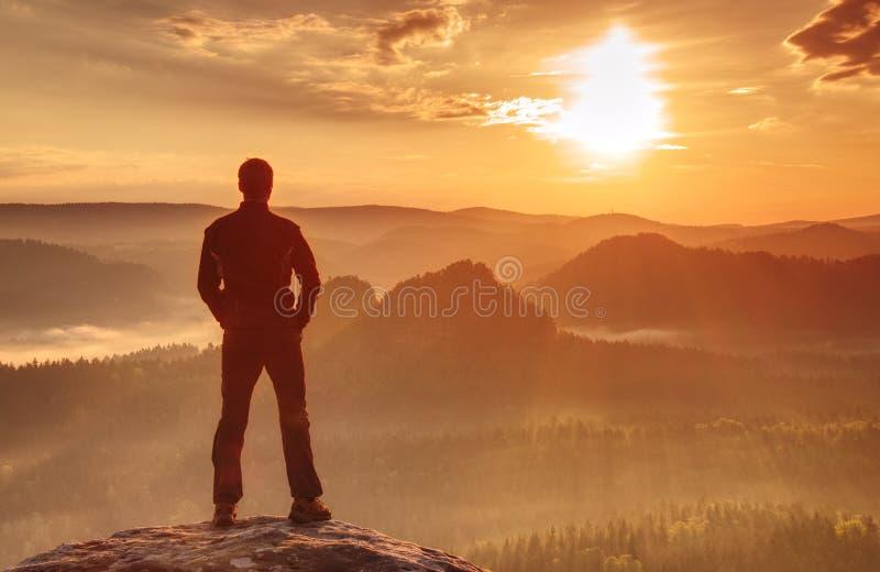 Den stiliga idrotts- mannen, en turist, stag på toppmöte vaggar Lös mist royaltyfri bild