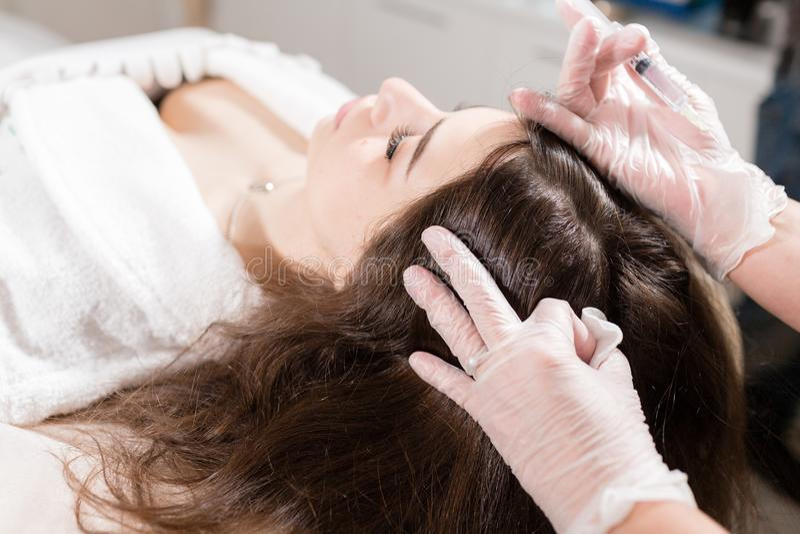 Den stiliga kvinnan mottar en injektion i huvudet Tillvägagångssättet gör doktorn i vita handskar Begreppet av mesotherapy arkivbilder