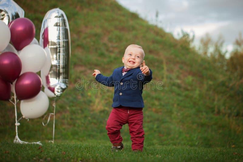 Den stiliga leendeståenden behandla som ett barn 1 åriga gulliga pojke på gräset Födelsedagårsdag arkivfoto