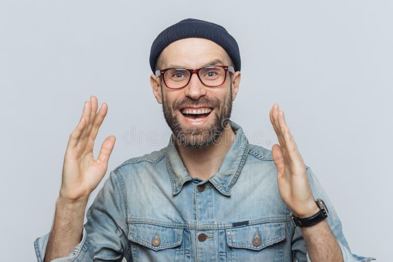 Den stiliga lyckliga mannen lyfter händer med spänning, har extatisk före detta arkivfoto