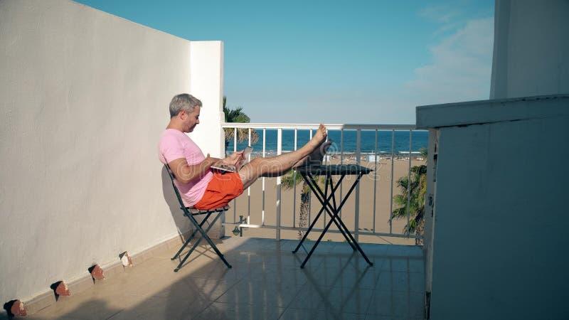 Den stiliga manliga freelanceren arbetar på hans bärbar dator, medan sitta på seaviewterrass arkivbild