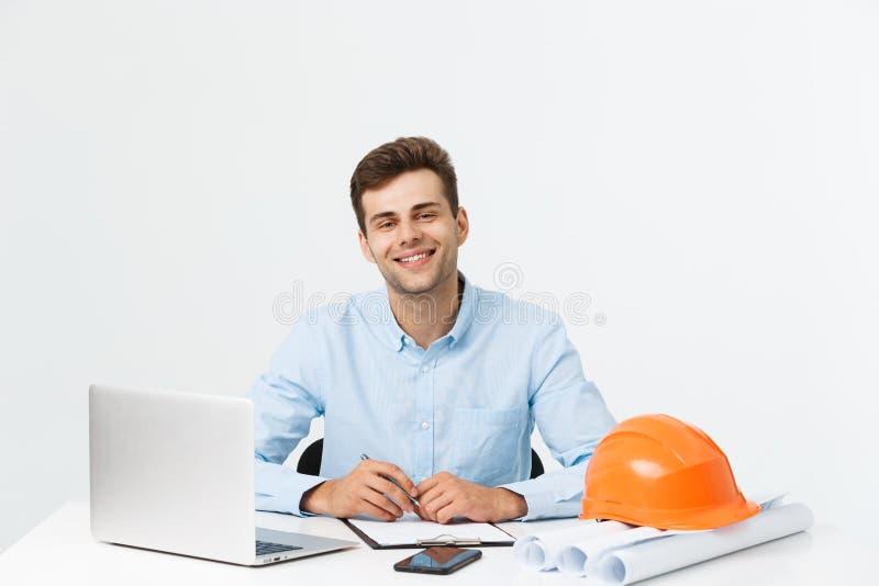 Den stiliga manliga teknikern använder en anteckningsbok för arbete Han sitter på skrivbordet och le Kopieringsutrymme på sida arkivfoton