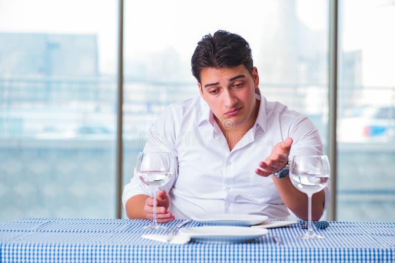 Den stiliga mannen bara i restaurang på datum royaltyfria foton