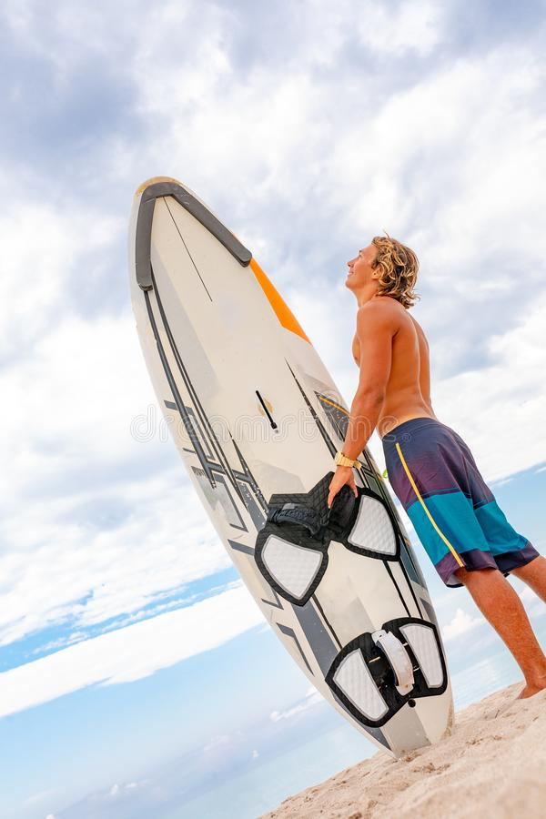Den stiliga mannen går med vitmellanrumssurfingbrädan väntar på vågen att surfa fläcken på havshavkusten Begrepp av sporten royaltyfri foto