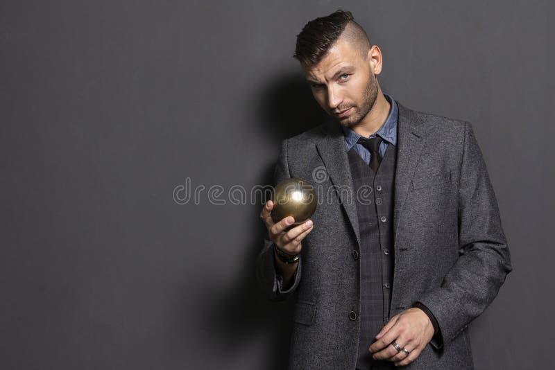 Den stiliga mannen i dräkt rymmer i guld- boll för hand Elegant manaffärslärare Trendig och stilfull säker man royaltyfri fotografi