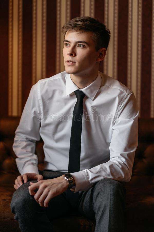 Den stiliga mannen i en affärsdräkt sitter på soffan royaltyfria bilder