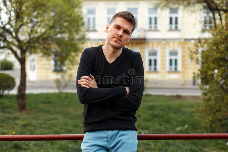 Den stiliga mannen i en svart T-tröja och blått flåsar i staden royaltyfri fotografi
