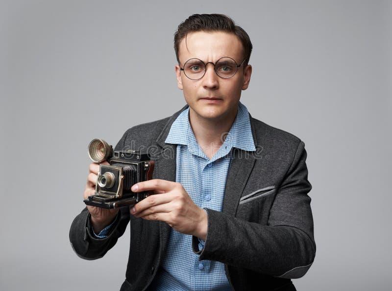 Den stiliga mannen i exponeringsglas rymmer en kamera arkivbilder