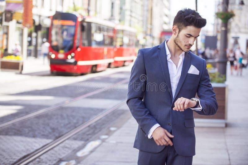 Den stiliga mannen klädde elegantly se hans klocka royaltyfri bild