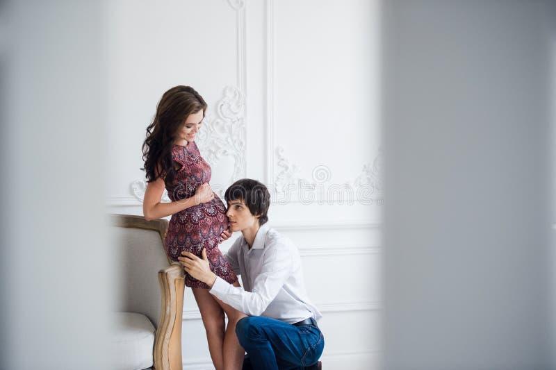 Den stiliga mannen lyssnar till hans härliga gravida mage och le för fru` s royaltyfri bild