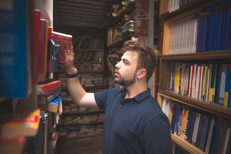 Den stiliga mannen med ett skägg är en bok från den atmosfäriska hyllan arkivfoto