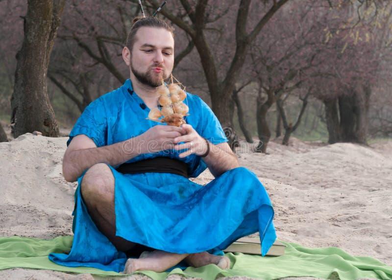 den stiliga mannen med utgör, hårbullen som sitter på sand i den blåa kimonot som ser skeppmodellen med snäckskal arkivbilder
