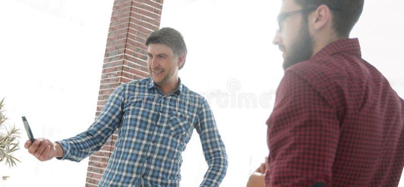 Den stiliga mannen pekar till whiteboarden i regeringsställning arkivfoto