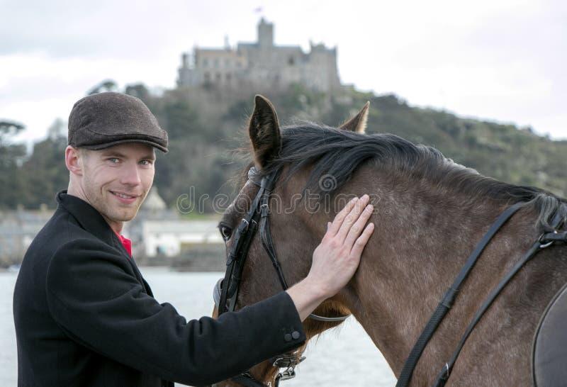 Den stiliga mannen, ryttaren för den manliga hästen daltar hans häst på stranden, det bärande traditionella plana locket, vit byx royaltyfri foto