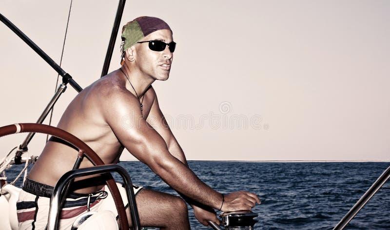Den stiliga mannen seglar på fartyget arkivbild