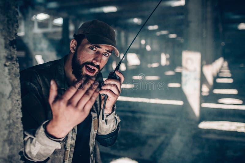 Den stiliga mannen ser rak på kamera Han är den hållande bärbara radion och samtal till det Också visar han hans rätt fotografering för bildbyråer