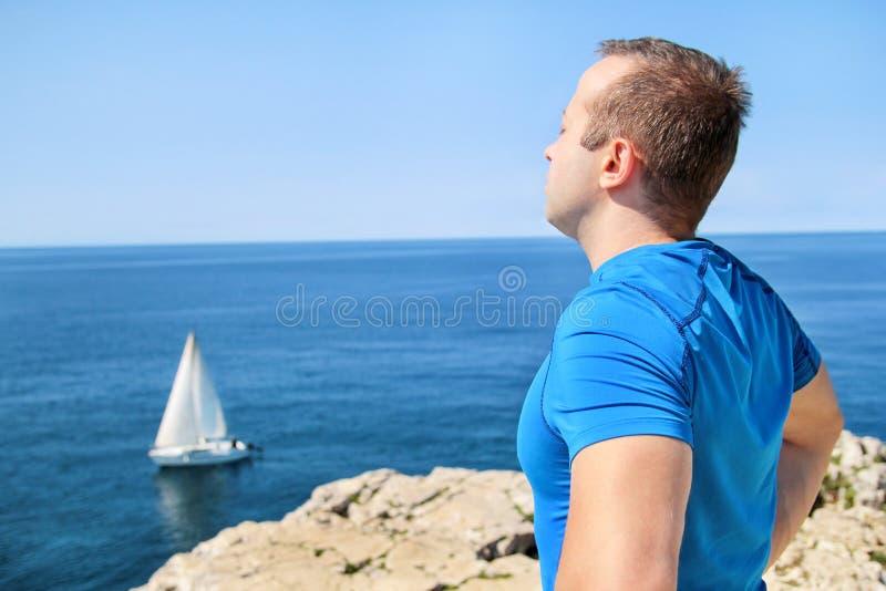 Den stiliga mannen som bär bekläda för sportar, tar ett avbrott efter en rinnande utbildning och tycker om härlig naturlig omgivn royaltyfri fotografi