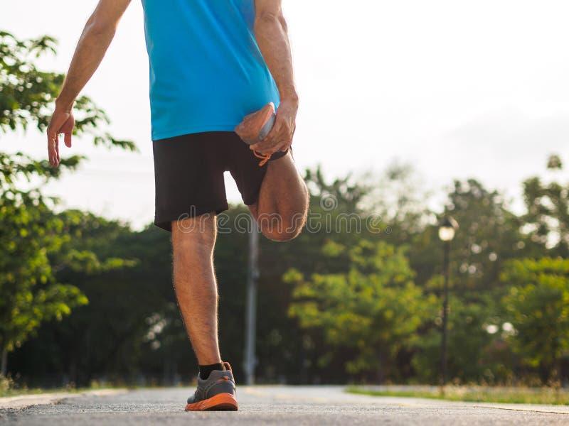 Den stiliga mannen sträcker, innan han joggar Kondition och livsstil royaltyfria foton
