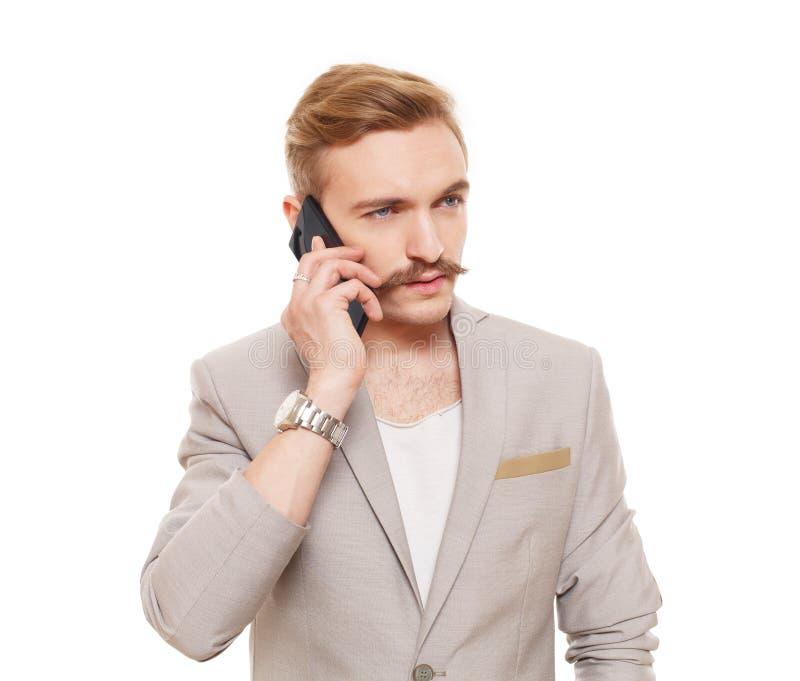 Den stiliga mannen talar på mobiltelefonen som isoleras på vit royaltyfria bilder