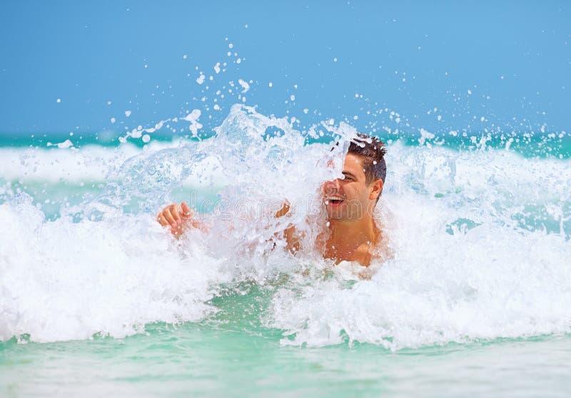 Den stiliga mannen tycker om att simma i havsvågor royaltyfri bild