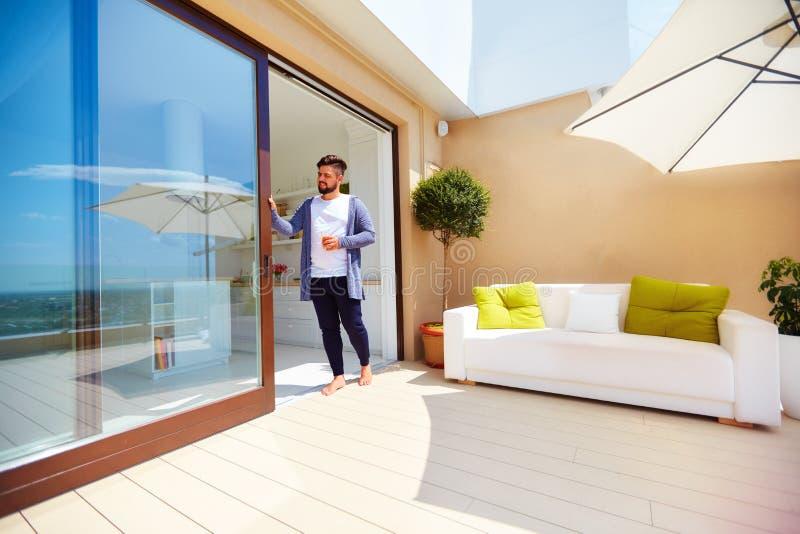 Den stiliga mannen tycker om liv på takterrass, med öppet utrymmekök- och glidningsdörrar royaltyfri bild
