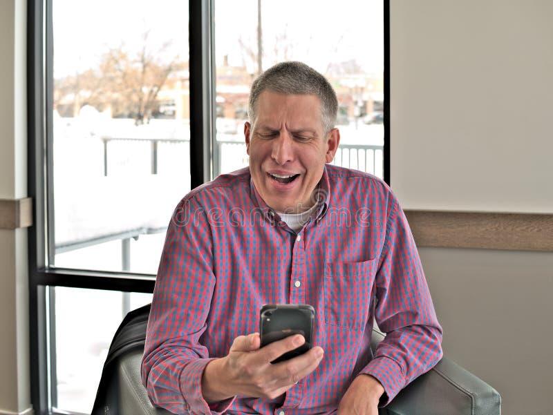 Den stiliga mellersta åldriga mannen i tillfällig kläder uttrycker emotionellt svar till ett meddelande på hans smarta mobila mob arkivfoton