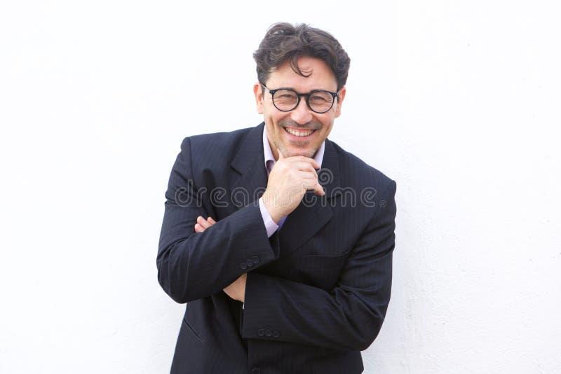 Den stiliga mitt åldrades affärsmannen som ler mot vit bakgrund arkivfoto