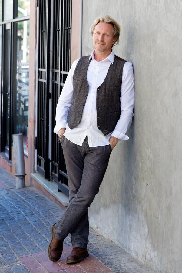 Den stiliga mitt åldrades mannen som lutar till väggen utanför på trottoaren royaltyfri foto