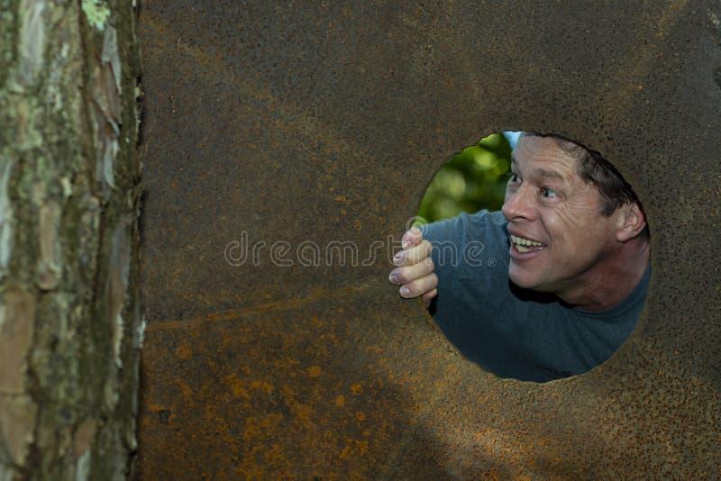 Den stiliga mogna mannen i järnplattahålet som bort ser, grinar, lyckligt, nöjt arkivfoto