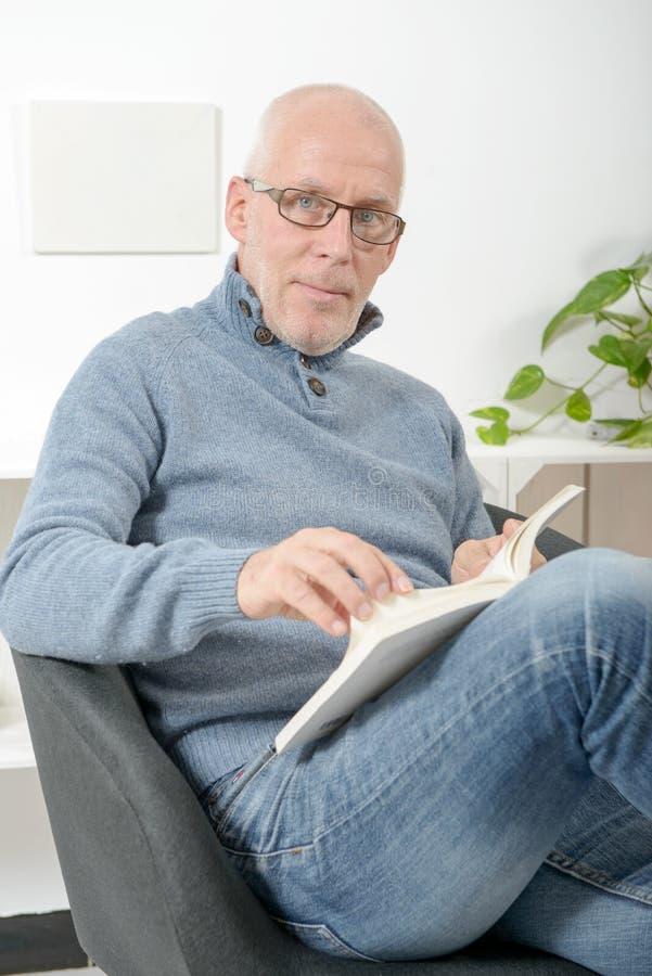 Den stiliga mogna mannen läste en bok royaltyfria foton