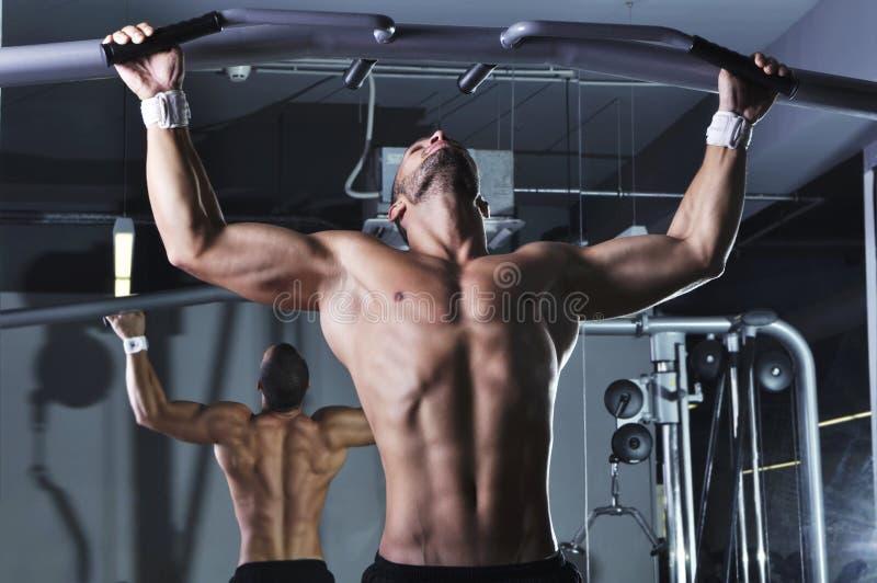 Den stiliga muskulösa manliga modellen With Perfect Body som gör handtag, Ups arkivbild
