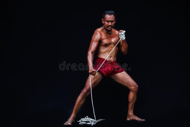 Den stiliga muskulösa mannen visar forntida asiatiska traditionella kampsporter, thailändsk boxning eller Muay thailändskt arkivfoto