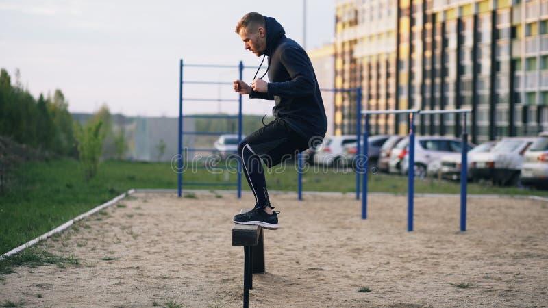 Den stiliga muskulösa unga mannen har crossfitutbildningsbanhoppning på stång på parkera fotografering för bildbyråer