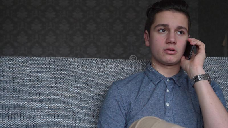 Den stiliga pojketonåringen som talar på telefonen, sitter på en grå soffa royaltyfria bilder