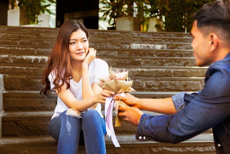 Den stiliga pojkvännen ger blommabuketten till flickvännen och honom royaltyfri foto