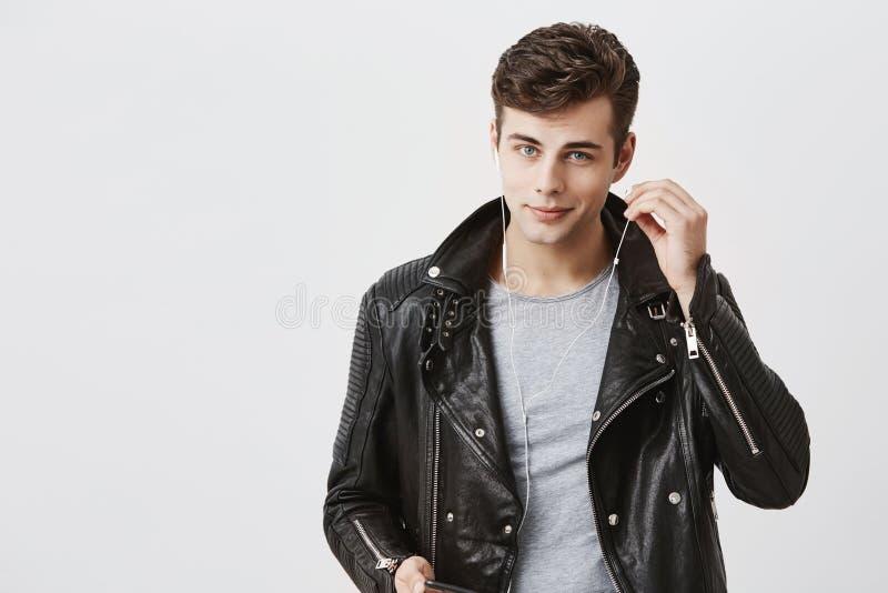 Den stiliga positiva mannen i svart läderomslag med svagt leende, lyssnar musik i hörlurar Den unga caucasian mannen tycker om royaltyfri fotografi