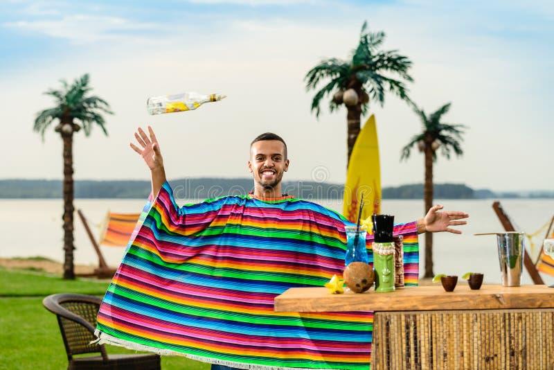 Den stiliga positiva mexicanska bartendern i färgrik poncho kastar upp royaltyfri fotografi