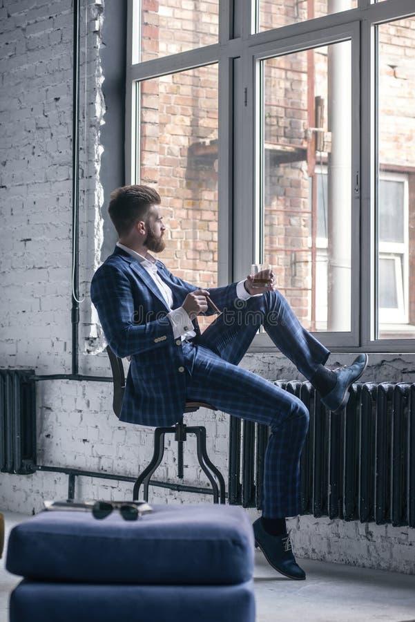 Den stiliga säkra mannen rymmer en cigarr och ett exponeringsglas av whisky och ser bort, medan placera på stolen och se till arkivbild