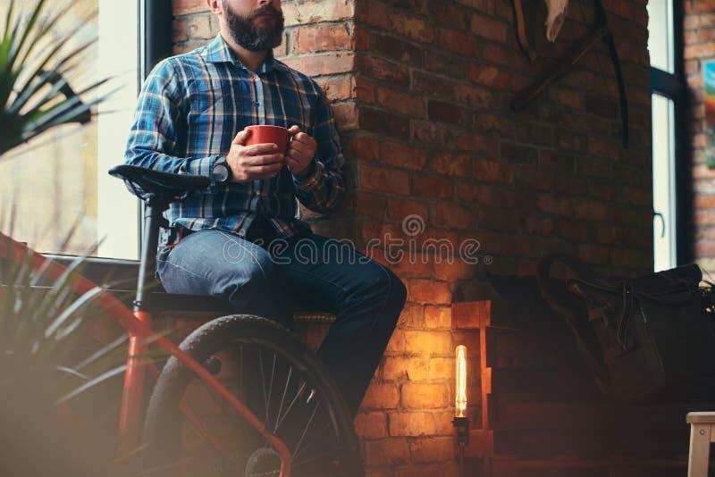 Den stiliga skäggiga hipstermannen i en blå ullbeklädnadskjorta och jeans rymmer en kopp av morgonkaffe, medan sitta på ett fönst royaltyfri bild