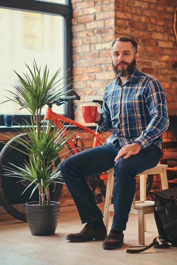 Den stiliga skäggiga hipstermannen i en blå ullbeklädnadskjorta och jeans rymmer en kopp av morgonkaffe, medan sitta på ett trä royaltyfria bilder