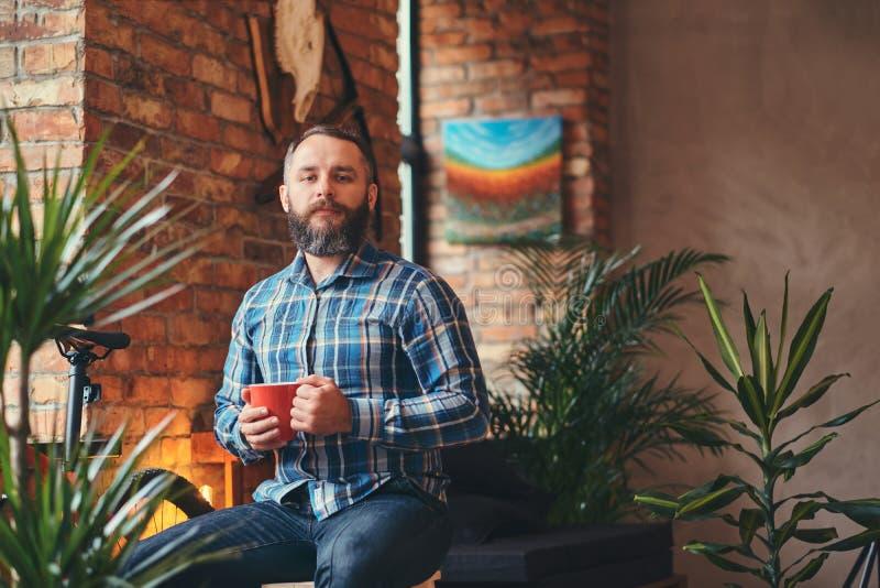 Den stiliga skäggiga hipstermannen i en blå ullbeklädnadskjorta och jeans rymmer en kopp av morgonkaffe, medan sitta på ett trä royaltyfri bild