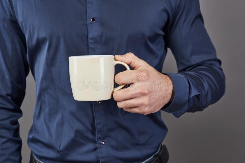 Den stiliga skäggiga mannen med det stilfulla hårskägget och mustaschen på allvarlig framsida i hållande vit kopp för skjorta ell royaltyfri foto