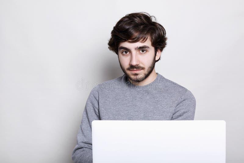 Den stiliga skäggiga mannen med sylish mörkt hår som bär den tillfälliga gråa tröjan som kontrollerar mejl på bärbara datorn som  royaltyfri foto